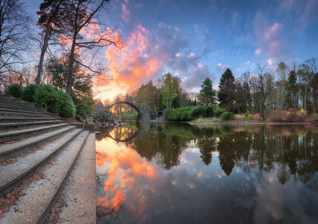 keystone: Devils Bridge in Kromlau, Germany. Amazing landscape with Rakotz Bridge, stairs, lake, green trees, colorful blue sky with multicolored clouds reflected in water at sunset in spring. Rakotzbrucke