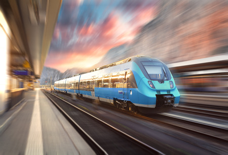 High speed train in motion at the railway station at sunset. Modern european intercity train on the railway platform with motion blur effect. Industrial landscape with blue passenger train on railroad 免版税图像