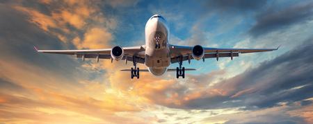 Landing vliegtuig. Landschap met wit passagiersvliegtuig vliegt in de blauwe lucht met wolken bij kleurrijke zonsondergang. Reis achtergrond. Passagiersvliegtuig. Zakenreis. Commercieel vliegtuig. Concept