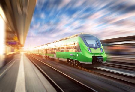 Treno ad alta velocità in movimento alla stazione ferroviaria al tramonto in Europa. Bello treno moderno verde sulla piattaforma ferroviaria con effetto di sfocatura di movimento. Scena industriale con treno passeggeri sulla ferrovia