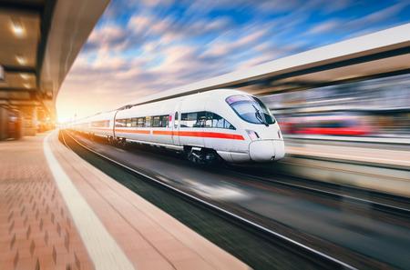 Weiße moderne Hochgeschwindigkeitszug in Bewegung auf Bahnhof bei Sonnenuntergang. Trainieren Sie am Abend auf Schienenbahn mit Bewegungsunschärfe in Europa. Bahnsteig. Industrielandschaft. Bahntourismus