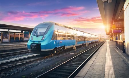 Nowożytna wysoka prędkość kolejka na staci kolejowej i kolorowy niebo z chmurami przy zmierzchem w Europa. Przemysłowy krajobraz z niebieskim pociągiem pasażerskim na platformie kolejowej. Tło kolejowe