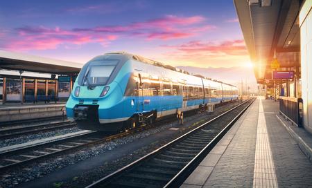 Treno pendolare ad alta velocità moderno sulla stazione ferroviaria e cielo variopinto con le nuvole al tramonto in Europa. Paesaggio industriale con treno passeggeri blu sulla piattaforma ferroviaria. Sfondo della ferrovia