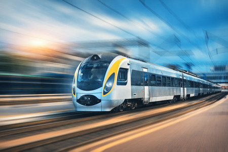 High speed train in motion at the railway station at sunset in Europe. Modern intercity train on the railway platform with motion blur effect. Industrial landscape with passenger train on railroad 免版税图像
