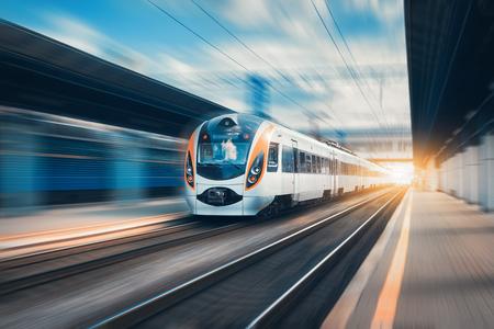 Hogesnelheidstrein bij het station bij zonsondergang in Europa. Moderne intercitytrein op spoorwegplatform. Stedelijke scène met mooie passagierstrein op spoorweg en gebouwen. Spoorweg landschap Stockfoto