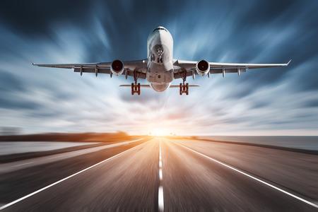 비행기와도 [NULL]로 모션 일몰 흐림 효과. 여객 비행기와 프리 아스팔트 도로 및 흐린 하늘 위로 날고있다. 상업 비행기가 착륙하고 있습니다. 흐린 배