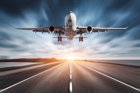 Airplane and road with motion blur effect at sunset. Landscape with passenger airplane is flying over the asphalt road and cloudy sky. Commercial plane is landing. Aircraft with blurred background Stock fotó