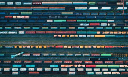 Lading treinen close-up. Luchtfoto van kleurrijke goederen treinen op het station. Wagons met goederen op de spoorweg. Zware industrie. Industriële conceptuele scène met treinen. Bovenaanzicht van vliegende drone Stockfoto
