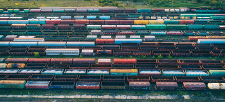Cargo trains close-up. Aerial view of colorful freight trains on the railway station. Wagons with goods on railroad. Heavy industry. Industrial conceptual scene with trains. Top view from flying drone Stock Photo