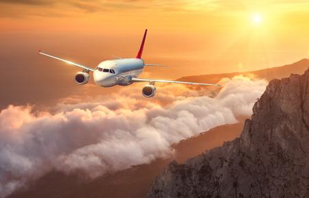 L'avion survolent les nuages ??au coucher du soleil. Paysage avec l'avion de passagers blanc, les montagnes, la mer et le ciel orange avec le soleil en été. L'avion de passagers atterrit. Voyage d'affaires. Avion commercial