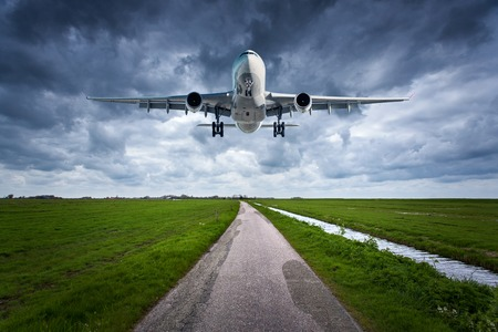Airplane and country road. Landscape with passenger airplane is flying over the asphalt road against cloudy sky, green grass. Travel. Passenger airliner is landing on the runway. Commercial plane