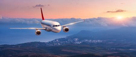 Passagiersvliegtuig. Landschap met wit vliegtuig vliegt in de oranje lucht met wolken over bergen, zee bij kleurrijke zonsondergang. Passagiersvliegtuig landt. Commercieel vliegtuig. Prive jet. Reizen