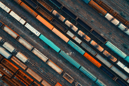 Aerial view of colorful freight trains on the railway station. Cargo trains close-up. Wagons with goods on railroad. Heavy industry. Industrial conceptual scene with trains. Top view. Vintage style