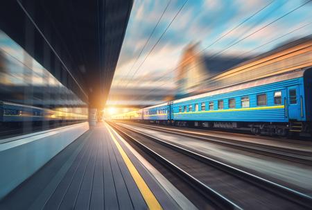 Mooie trein met blauwe wagens in motie bij het station bij zonsondergang. Industriële mening met moderne trein, spoorweg, spoorwegplatform, gebouwen, bewolkte hemel met het effect van het motieonduidelijke beeld. Concept