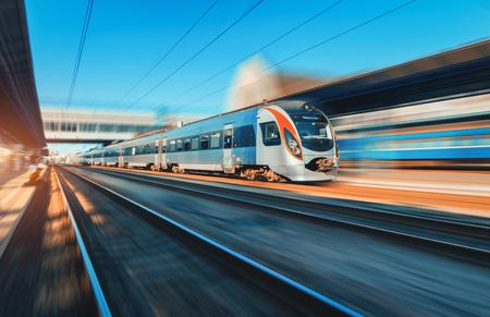 Hoge snelheidstrein in motie bij het station bij zonsondergang in Europa. Moderne intercitytrein op het spoorwegplatform met motieonduidelijk beeldeffect. Industriële scène met bewegende passagierstrein op spoorweg