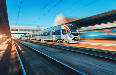 Train à grande vitesse en mouvement à la gare au coucher du soleil en Europe. Train interurbain moderne sur la plate-forme ferroviaire avec effet de flou de mouvement. Scène industrielle avec le train de voyageurs en mouvement sur le chemin de fer Banque d'images - 89457130