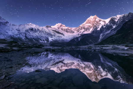 Amazing night scene with himalayan mountains and mountain lake at starry night in Nepal. Landscape with high rocks with snowy peak and sky with stars reflected in water. Beautiful Manaslu, Himalayas Stock Photo