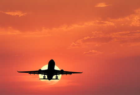 Silhouette of landing aircraft and red sky with sun. Landscape with passenger airplane is flying in the sky with clouds at sunset. Travel background. Passenger airliner. Commercial airplane. Business Stock Photo