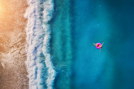 Aerial view of young woman swimming on the pink swim ring in the transparent turquoise sea in Oludeniz. Summer seascape with girl, beach, beautiful waves, blue water at sunset. Top view from drone Archivio Fotografico