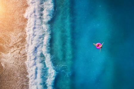 Luchtfoto van jonge vrouw zwemmen op het roze zwemmen ring in de transparante turquoise zee in Oludeniz. Zomer zeegezicht met meisje, strand, mooie golven, blauw water bij zonsondergang. Bovenaanzicht van drone Stockfoto