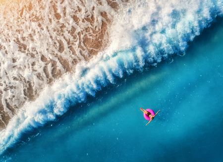 Aerial view of young woman swimming on the pink swim ring in the transparent blue sea in Oludeniz,Turkey. Summer seascape with girl, beautiful waves, azure water at sunset. Top view from drone. Travel
