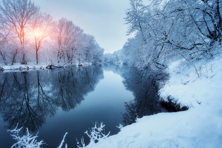 Winter forest on the river at sunset. Colorful landscape with snowy trees, frozen river with reflection in water. Seasonal. Snow covered trees, lake, sun and blue sky. Beautiful forest in snowy winter