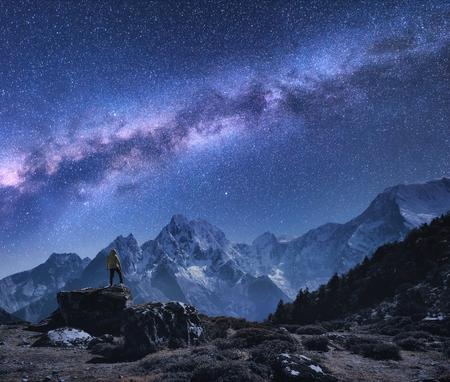 Espacio con vía láctea y montañas. Hombre derecho en la piedra, las montañas y el cielo estrellado en la noche en Nepal. Rocas con picos nevados contra el cielo con estrellas. Trekking. Paisaje nocturno con brillante vía láctea. Foto de archivo