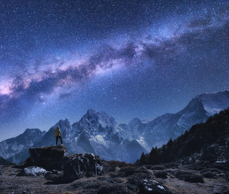 Space with Milky Way and mountains. Standing man on the stone, mountains and starry sky at night in Nepal. Rocks with snowy peaks against sky with stars. Trekking.Night landscape with bright milky way Stock Photo