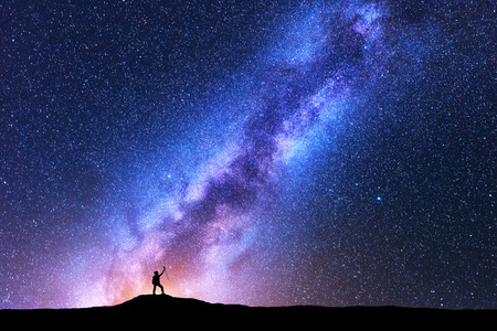 Silhouette of happy woman with trekking poles against purple Milky Way at night. Space background. Landscape with girl on the mountain, bright milky way, sky with stars. Galaxy. Travel. Starry sky Stock Photo