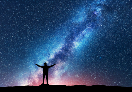 Space. Milky Way with silhouette of a standing happy man with raised up arms on the hill. Night landscape with beautiful galaxy. Universe. Night sky with stars, colorful Milky Way. Starry sky and man