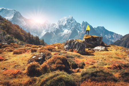 Standing man on the stone and looking on amazing Himalayan mountains at sunset. Landscape with traveler, high rocks with snowy peaks, plants, forest in autumn in Nepal. Lifestyle, travel. Trekking Stock Photo
