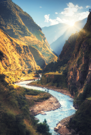 Colorful landscape with high Himalayan mountains, beautiful curving river, green forest, blue sky with clouds and yellow sunlight at sunset in autumn in Nepal. Mountain valley. Travel in Himalayas