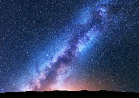 Milky Way. Fantastic night landscape with bright milky way, sky full of stars, yellow light and hills. Shiny stars. Beautiful scene with universe. Space background with starry sky. Astrophotography