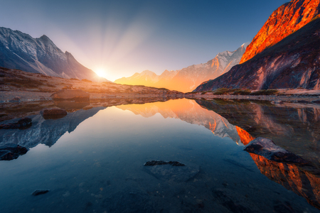 Beautiful landscape with high mountains with illuminated peaks, stones in mountain lake, reflection, blue sky and yellow sunlight in sunrise. Nepal. Amazing scene with Himalayan mountains. Himalayas Banco de Imagens
