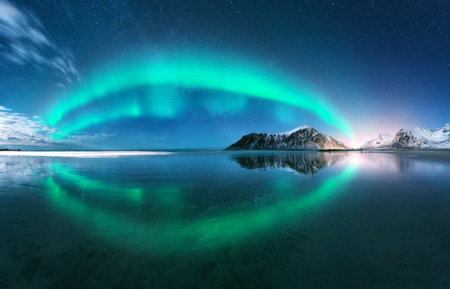 Aurora. Northern lights in Lofoten islands, Norway. Starry blue sky with polar lights. Night winter landscape with aurora, sea with sky reflection, beach, mountains, city lights. Green aurora borealis