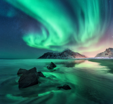 Aurora. Northern lights in Lofoten islands, Norway. Sky with polar lights, stars. Night winter landscape with aurora, sea with sky reflection, stones, sandy beach and mountains. Green aurora borealis