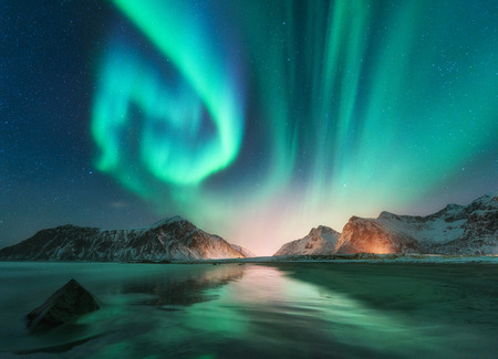 Aurora borealis in Lofoten islands, Norway. Aurora. Green northern lights. Starry sky with polar lights. Night winter landscape with aurora, sea with sky reflection, stones, beach and snowy mountains 스톡 콘텐츠