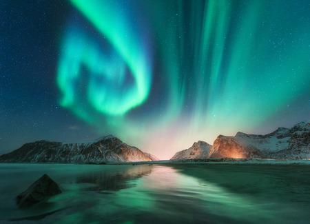 Zorza polarna na Lofotach, Norwegia. Zorza polarna. Zielone zorza polarna. Gwiaździste niebo z polarnymi światłami. Nocny zimowy krajobraz z zorzą polarną, morze z odbiciem nieba, kamienie, plaża i zaśnieżone góry Zdjęcie Seryjne