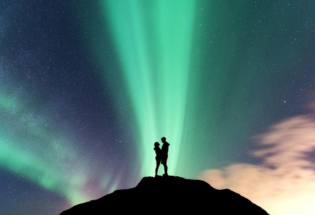 Aurora and hugging couple on the mountain peak. Landscape with night starry sky, aurora borealis, silhouette of man and woman. People against bright northern lights. Lovers and polar lights. Concept