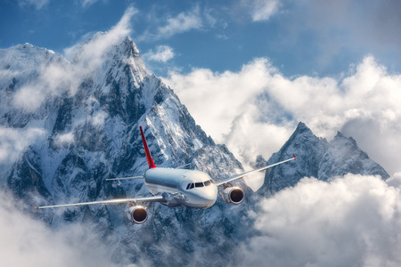 Airplane is flying over low clouds against mountains with snowy peaks in bright day. Landscape. Passenger airplane, cloudy sky, rocks, snow. Passenger aircraft. Business, commercial travel.Aerial view 免版税图像