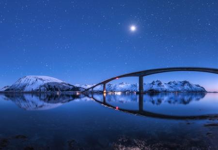 Niesamowity most i gwiaździste niebo z pięknym odbiciem w wodzie. Nocny krajobraz z mostem, zaśnieżonymi górami, błękitnym niebem z księżycem i jasnymi gwiazdami odbitymi w morzu. Zima na Lofotach w Norwegii