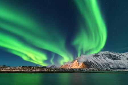 Aurora borealis. Lofoten islands, Norway. Aurora. Green northern lights. Starry sky with polar lights. Night winter landscape with aurora, sea with sky reflection and snowy mountains. Nature. Travel Standard-Bild - 98682743
