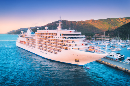 Cruise ship at harbor. Aerial view of beautiful large white ship at sunset. Landscape with boats, mountains, sea, blue sky. Top view of yacht. Luxury cruise. Floating liner in Europe. Travel. Resort Zdjęcie Seryjne