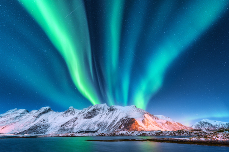 Aurora borealis. Lofoten islands, Norway. Aurora. Green northern lights. Starry sky with polar lights. Night winter landscape with aurora, sea with sky reflection and snowy mountains.Nature background