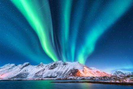 Aurora boreale. Isole Lofoten, Norvegia. Aurora. Aurora boreale verde. Cielo stellato con luci polari. Paesaggio invernale di notte con aurora, mare con la riflessione del cielo e montagne innevate. Sfondo naturale Archivio Fotografico - 99968923