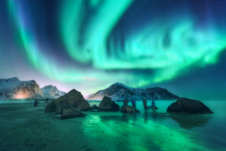 Green aurora borealis and photographers. Aurora. Northern lights in Lofoten islands, Norway. Starry sky with polar lights. Night landscape with aurora, sea, people, stones, sandy beach and mountains.