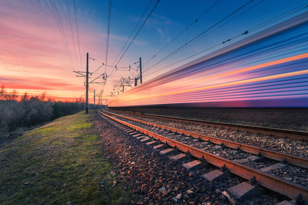 High speed passenger train in motion on railroad at sunset. Blurred modern commuter train. Railway station and colorful sky. Railroad travel, railway tourism. Industrial landscape. Transportation