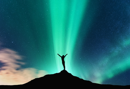 Aurora and silhouette of standing woman with raised up arms on the mountain in Norway. Aurora borealis and happy girl. Starry sky, green polar lights. Night landscape. Northern lights. Travel Banque d'images