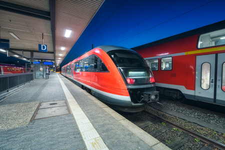 High speed train on the railway station at night in Nuremberg, Germany. Modern intercity train on the railway platform with illumintain. Commuter red train on railroad. Passenger transportation. Dusk Stock Photo