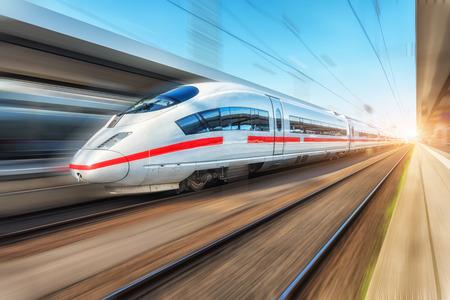 Weißer moderner Hochgeschwindigkeitszug in Bewegung am Bahnhof bei Sonnenuntergang. Personenzug auf Eisenbahnschiene mit Bewegungsunschärfeeffekt in Europa. Bahnsteig. Industrielandschaft. Eisenbahntourismus